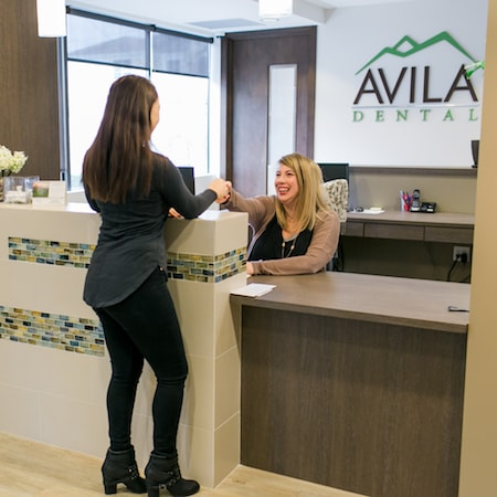 woman greeting the front desk at Avila Dental